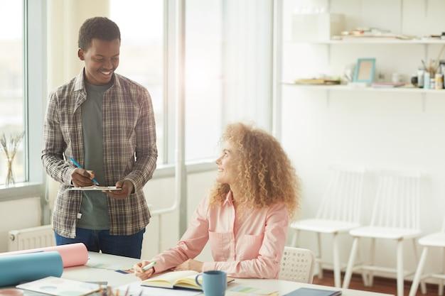 Portret wesoły afrykańsko-amerykański student patrząc na kręcone włosy dziewczyny podczas omawiania kreatywnego projektu w nowoczesnym białym biurze, kopia przestrzeń