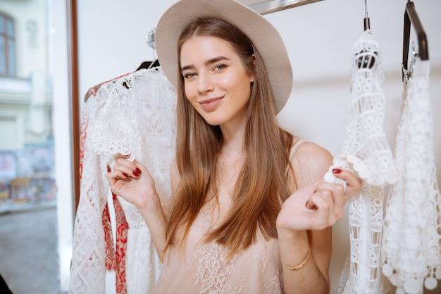 Portret wesoły całkiem młoda kobieta robi zakupy w sklepie odzieżowym