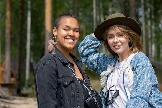Portret wesoły całkiem wieloetnicznych dziewcząt w kurtkach stojących na wietrze, podziwiając spacer w lesie