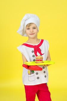 Portret wesoły chłopak gotować z burger na tacy na żółtej ścianie. szef kuchni w czerwonym mundurze. różne zawody