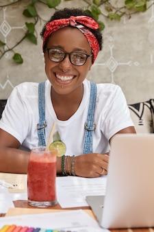 Portret wesoły czarny student odrabia lekcje w przytulnej kawiarni