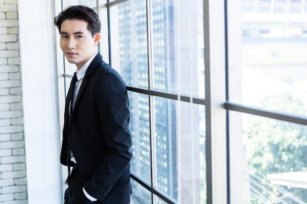 Portret wesoły dojrzały azjatycki młody biznesmen nosić garnitur mężczyzny w niebieskiej kurtce i niebieskiej koszuli patrząc przez okno w tle pokoju biurowego.