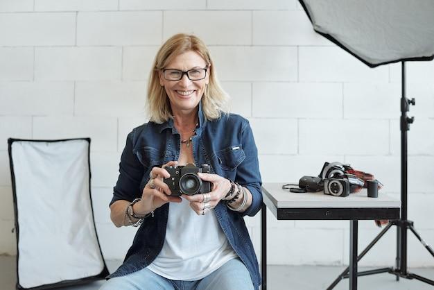 Portret wesoły dojrzały fotograf w okularach, siedząc w sesji zdjęciowej i za pomocą aparatu
