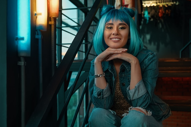 Portret wesoły dziewczyna o stylowych niebieskich włosach i ładnej twarzy