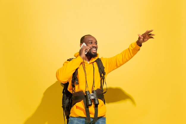 Portret wesoły facet młody turysta z torbą i lornetką na białym tle na żółtej ścianie studia