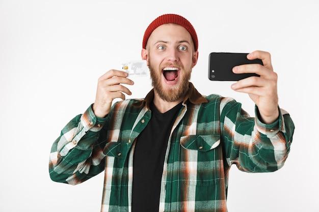 Portret wesoły facet na sobie koszulę w kratę, trzymając kartę kredytową i telefon komórkowy, stojąc na białym tle nad białym tle