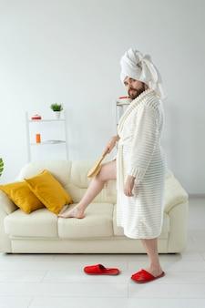 Portret wesoły facet nosić ręcznik turban robi sobie masaż za pomocą pędzla do masażu. pielęgnacja męskiej skóry i koncepcja spa