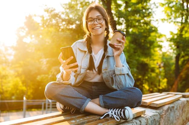 Portret wesoły ładny młody student dziewczyna nosi okulary siedzi na zewnątrz w parku przyrody przy użyciu telefonu komórkowego picia kawy.