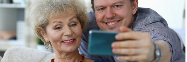 Portret wesoły matka i syn biorąc selfie do zapamiętania. uśmiechnięta starsza kobieta pozuje do zdjęcia na kanapie w domu. relacje rodzinne i koncepcja czasu wolnego