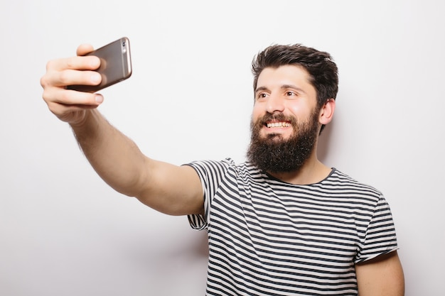 Portret wesoły mężczyzna dorywczo co selfie zdjęcie na smartfonie na białym tle na białej ścianie