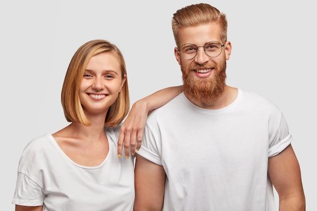 Portret wesoły młoda kobieta i przyjaciele mężczyzna bawią się razem, ubrani w strój casual, na białym tle nad białą ścianą