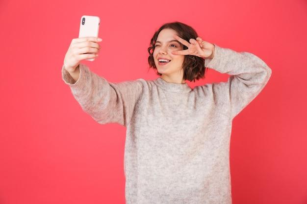 Portret wesoły młoda kobieta stojąca na białym tle nad różowym, biorąc selfie