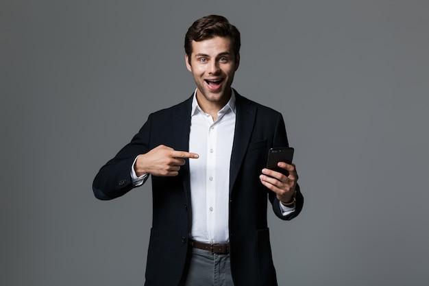 Portret wesoły młody biznesmen ubrany w garnitur na białym tle nad szarą ścianą, wskazując palcem na telefon komórkowy