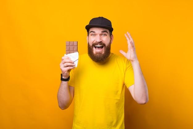 Portret wesoły młody brodaty mężczyzna trzyma tabliczkę czekolady na żółtej ścianie