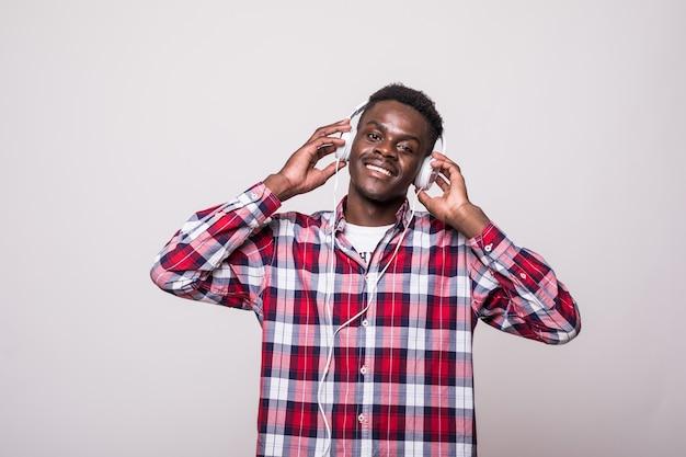 Portret wesoły młody człowiek afro amerykański, słuchanie muzyki w słuchawkach i śpiew na białym tle