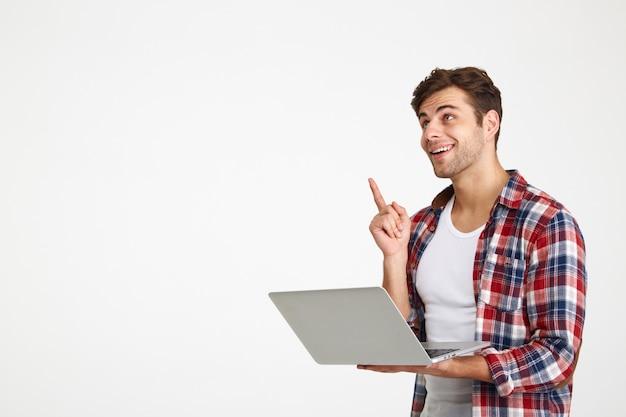 Portret wesoły młody człowiek posiadający laptopa