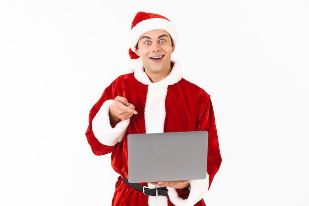 Portret wesoły młody człowiek ubrany w strój świętego mikołaja stojący na białym tle nad białą przestrzenią, trzymając laptopa
