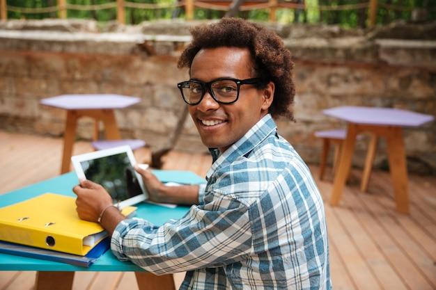 Portret wesoły młody człowiek w okularach, uśmiechając się i za pomocą tabletu