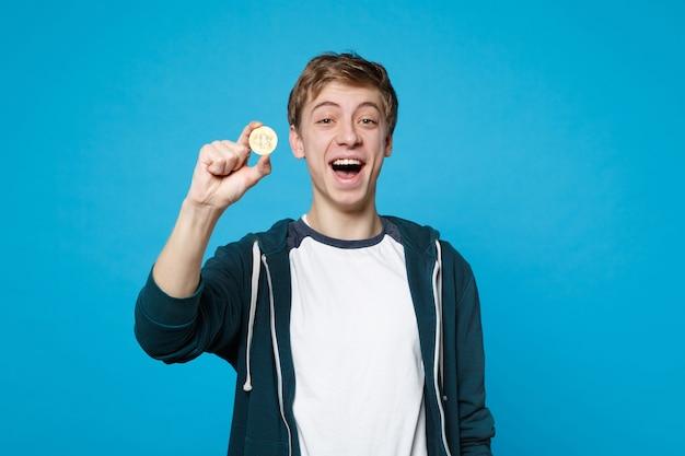 Portret wesoły młody człowiek w ubranie trzyma bitcoin, przyszła waluta na białym tle na ścianie niebieskiej. ludzie szczere emocje, koncepcja stylu życia.
