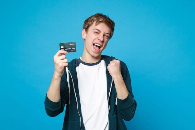 Portret wesoły młody człowiek w ubranie, trzymając kartę kredytową, zaciskając pięści jak zwycięzca na białym tle na ścianie niebieskiej. ludzie szczere emocje, koncepcja stylu życia.
