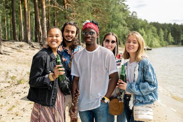 Portret wesoły młody międzyrasowy przyjaciele stojąc z butelkami piwa na plaży
