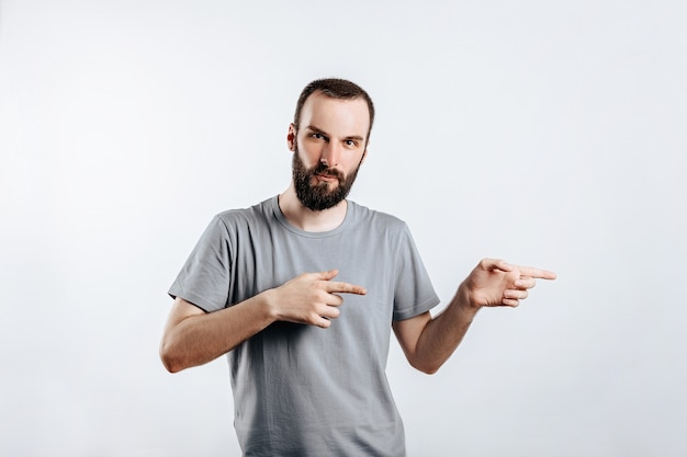 Portret wesoły młody przystojny mężczyzna uśmiechający się patrząc na kamerę wskazującą palcem w bok na białym tle z miejscem na reklamę makiety