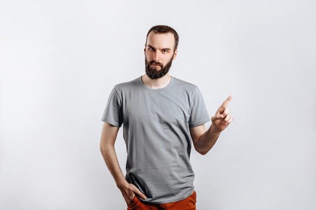 Portret wesoły młody przystojny mężczyzna uśmiechający się patrząc na kamerę wskazującą palcem w górę na białym tle z miejscem na reklamę makiety