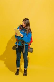 Portret wesoły młody turysta kaukaski dziewczyna z torbą i lornetką na białym tle na żółtym tle studio.