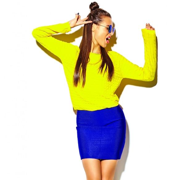 Portret wesoły moda hipster dziewczyna wariuje w dorywczo kolorowe żółte letnie ubrania z czerwonymi ustami na białym tle