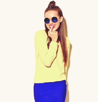 Portret wesoły moda uśmiechnięta hipster dziewczyna szaleje w codziennych kolorowe żółte letnie ubrania z czerwonymi ustami na białym gryząc palcem