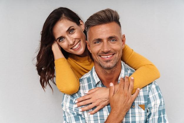 Portret wesoły optymistyczny dorosły kochający para na białym tle nad szarą ścianą.