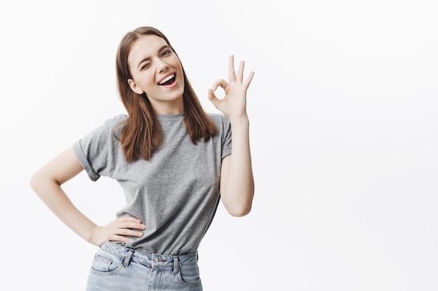 Portret wesoły piękna młoda dziewczyna brunetka o średnich długościach włosów w stylowe ubrania mrugania, z zadowolonym i radosnym wyrazem, pokazując ok gest ręką.