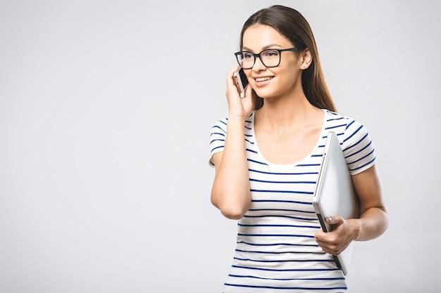 Portret wesoły piękna młoda kobieta z laptopa przy użyciu telefonu komórkowego, uśmiechając się