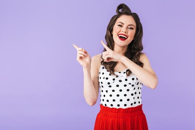 Portret wesoły pin-up kobieta w sukienka vintage w kropki wskazując palcami na bok na lato na białym tle nad fioletową ścianą