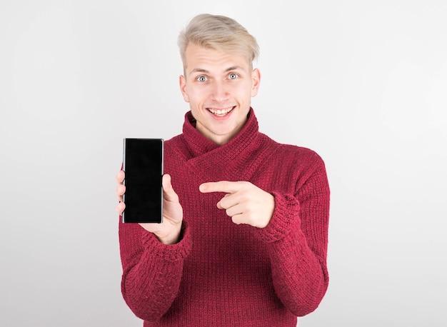 Portret wesoły, pozytywny, atrakcyjny facet z zarostem w czerwonym swetrze trzyma smartfona