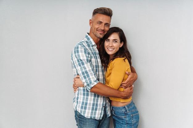 Portret wesoły pozytywny dorosły kochający para przytulanie na białym tle nad szarą ścianą.