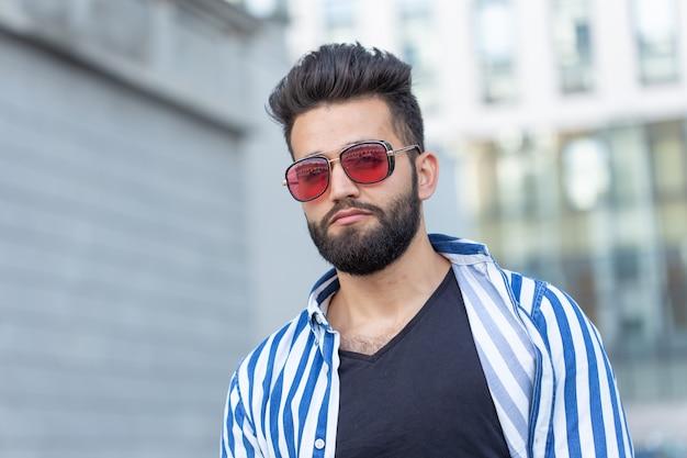 Portret wesoły pozytywny stylowy facet student w okularach z wąsem i brodą na zewnątrz. pojęcie udanych wesołych ludzi.