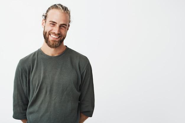 Portret wesoły przystojny brodaty facet z modną fryzurę uśmiecha się