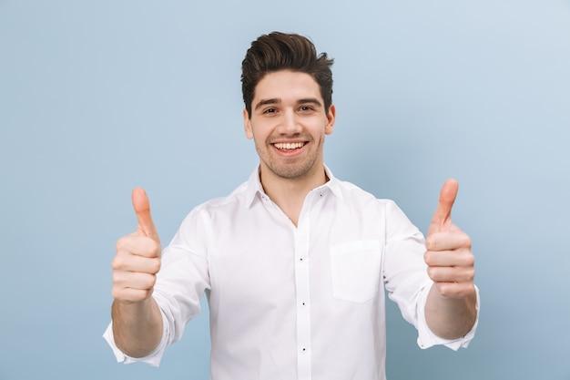 Portret wesoły przystojny młody człowiek stojący na białym tle na niebiesko, dając kciuki do góry