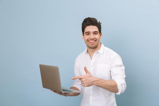 Portret wesoły przystojny młody człowiek stojący na białym tle na niebiesko, pracując na komputerze przenośnym