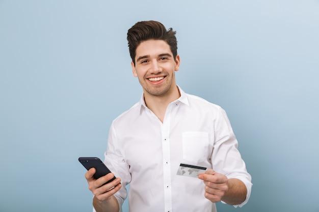 Portret wesoły przystojny młody człowiek stojący na białym tle na niebiesko, trzymając kartę kredytową, przy użyciu telefonu komórkowego