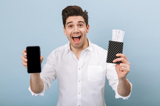 Portret wesoły przystojny młody człowiek stojący na białym tle na niebiesko, trzymając paszport z biletami lotniczymi, pokazując pusty ekran telefonu komórkowego