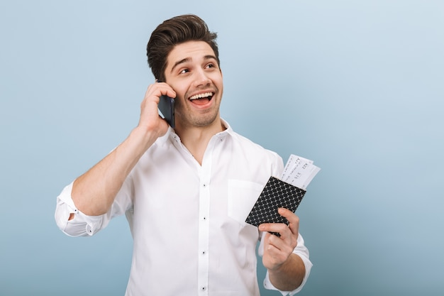Portret wesoły przystojny młody człowiek stojący na białym tle na niebiesko, trzymając paszport z biletami lotniczymi, przy użyciu telefonu komórkowego