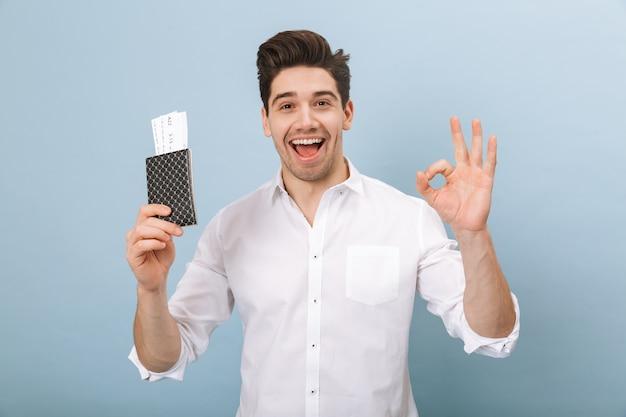 Portret wesoły przystojny młody człowiek stojący na białym tle na niebiesko, trzymając paszport z biletami lotniczymi