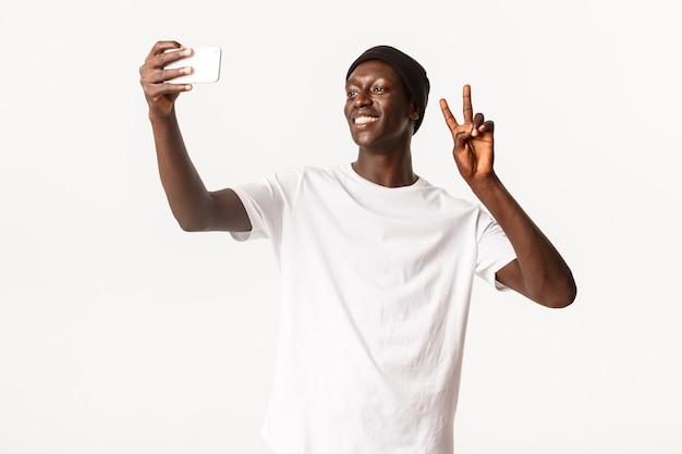 Portret Wesoły Przystojny Murzyn W Czapce, Biorąc Selfie Na Telefon Komórkowy I Pokazując Gest Pokoju Szczęśliwy, Uśmiechnięty Premium Zdjęcia