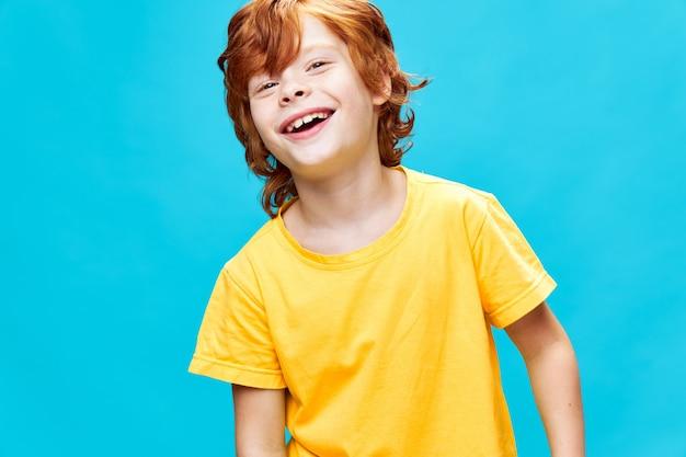 Portret wesoły rudy chłopiec z otwartymi ustami żółta koszulka przycięta widok niebieska na białym tle ściana