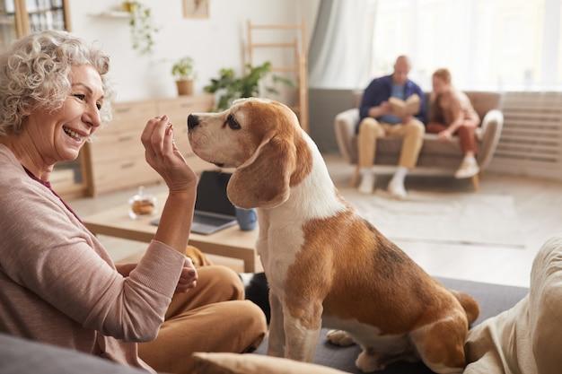 Portret wesoły starszy kobieta bawi się z psem i dając smakołyki, ciesząc się razem czas w domu