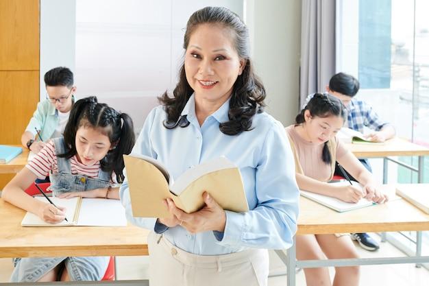 Portret wesoły starszy nauczyciel czytanie książki dla uczniów w klasie