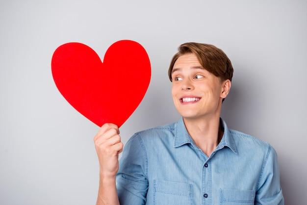 Portret wesoły szczery facet czuć się nieśmiały trzymać duże czerwone serce karty papieru