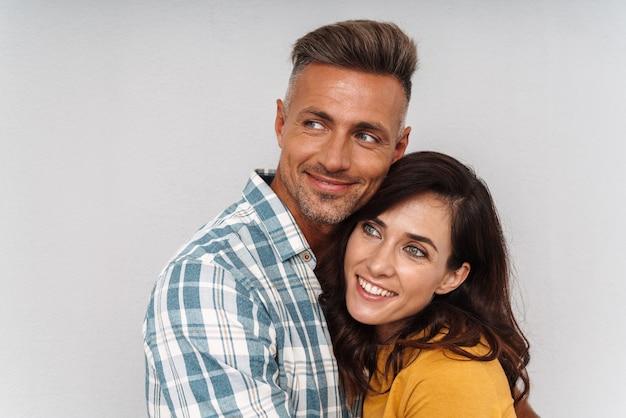 Portret wesoły szczęśliwy dorosłych miłości para na białym tle nad szarą ścianą.